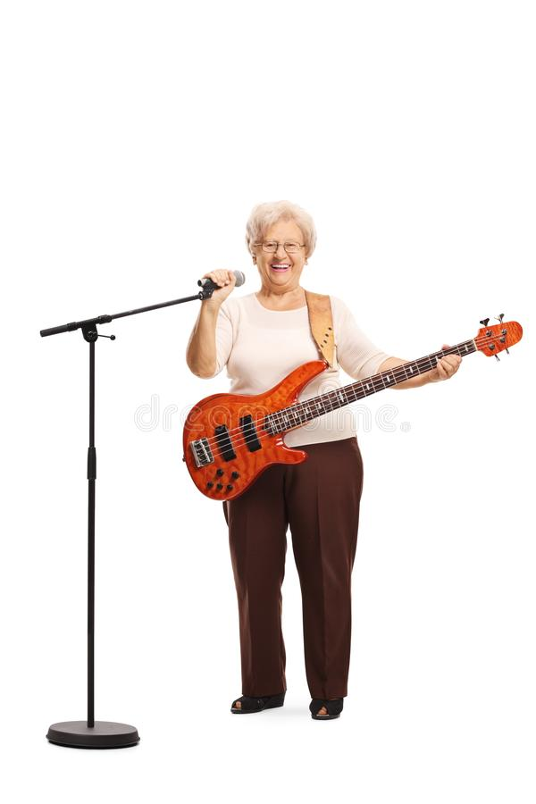 Elderly lady with a bass guitar holding a microphone. Full length portrait of an elderly lady with a bass guitar holding a microphone isolated on white royalty free stock photos