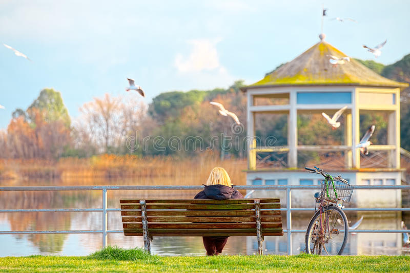 Elderly lady on a bench by the lake Torre del Lago Puccini stock photos