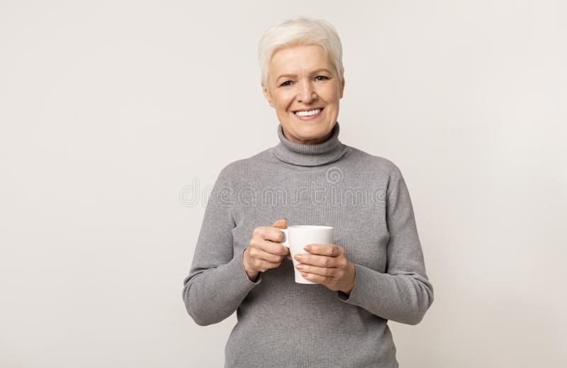 Elderly lady with cup of tea over light studio background stock photos