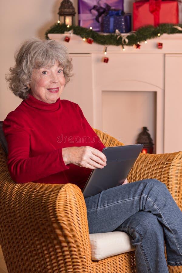 Elderly lady e-book reader Christmas imagen de archivo