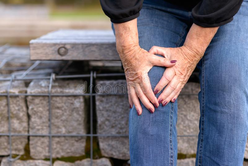 Elderly lady grabbing her knee in pain royalty free stock photo