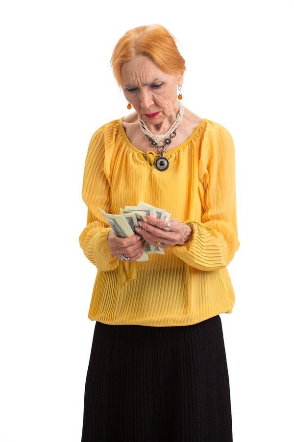 Elderly lady holding money isolated. royalty free stock image