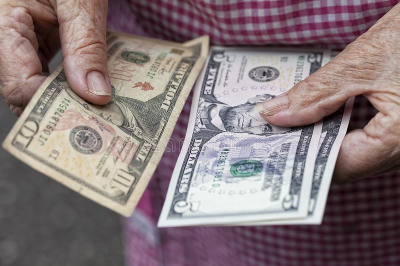 An elderly lady holds 20 dollars stock images