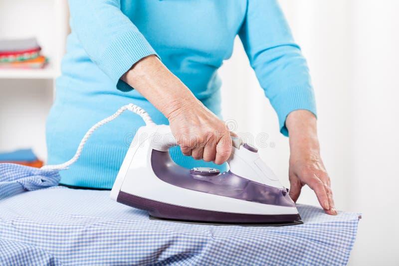 Elderly lady during ironing stock photography