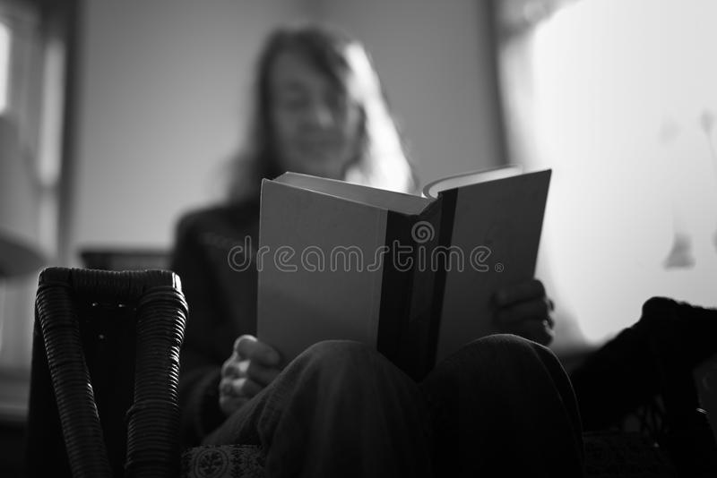 Elderly lady reading a book stock image