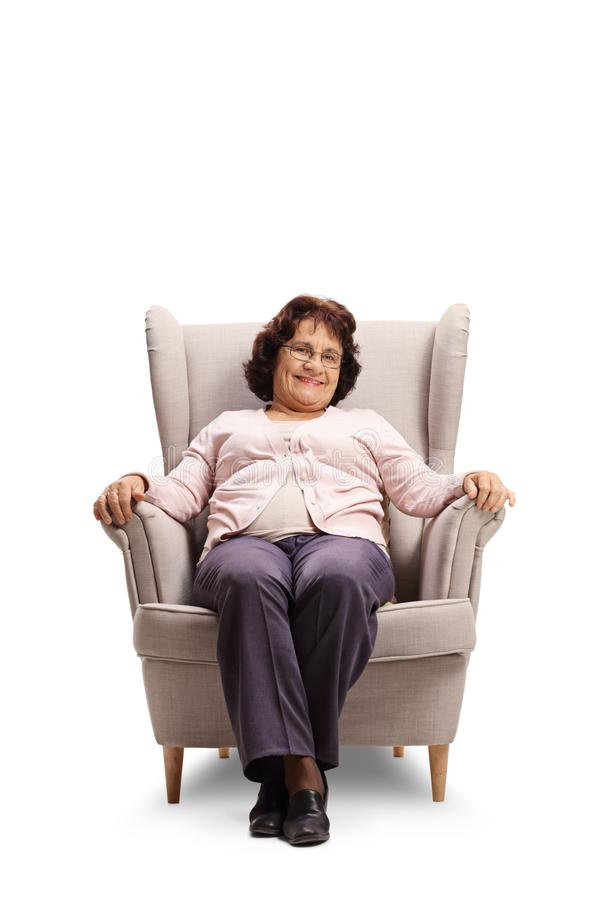 Elderly lady smiling and sitting in an armchair royalty free stock photography