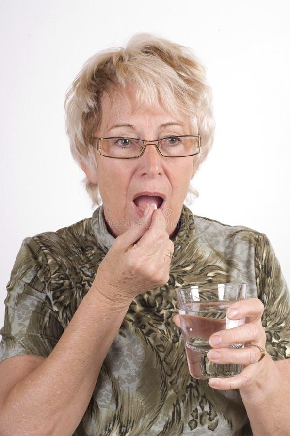 Elderly lady taking medicine royalty free stock photography