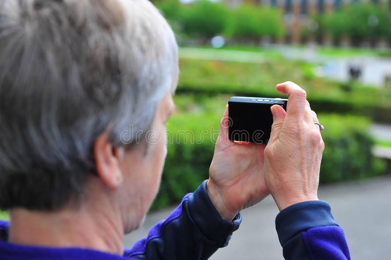 Elderly lady taking a picture stock image