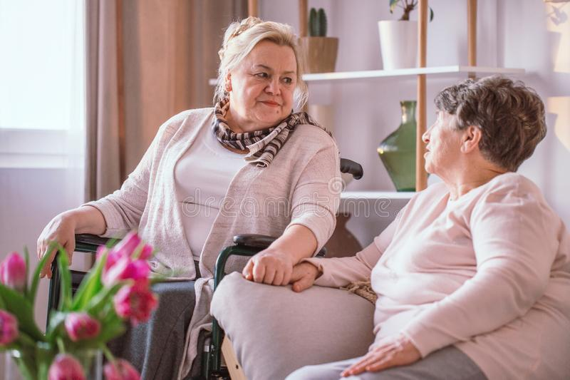 Elderly lady on the wheelchair holding hand her friend in nursing home. Interior stock images