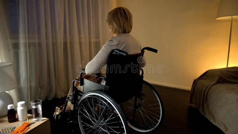 Elderly lady in wheelchair looking though window feeling lonely and depressed royalty free stock photo