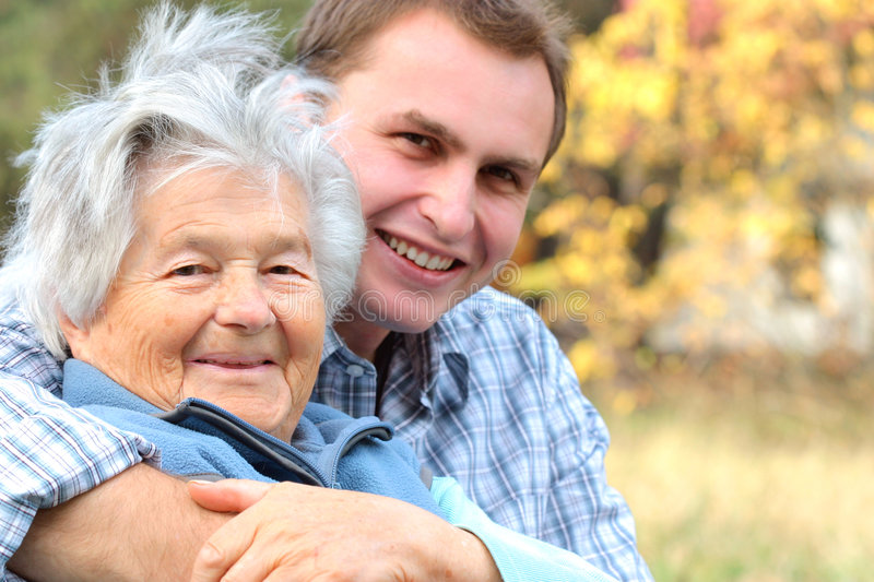 Elderly lady and young man. An elderly person hugged by her grandson.Focus on woman royalty free stock photos