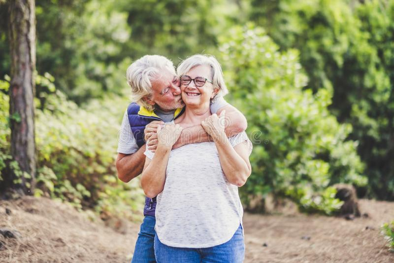 Elderly lifestyle people with couple of caucasian active senior kissing in relationship with green plants nature in background -. Elderly lifestyle people with stock image