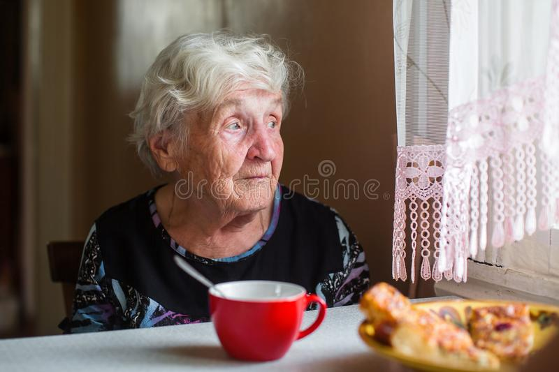 An elderly lone woman near the window with a Cup of tea. royalty free stock photo