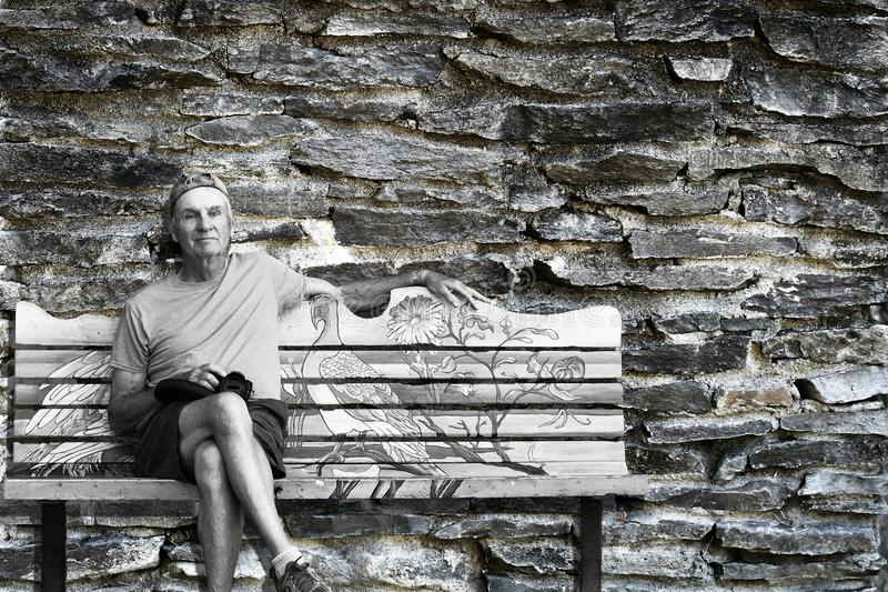 Elderly lonely man sits on bench with old grungy stone brick wall in the background royalty free stock photos