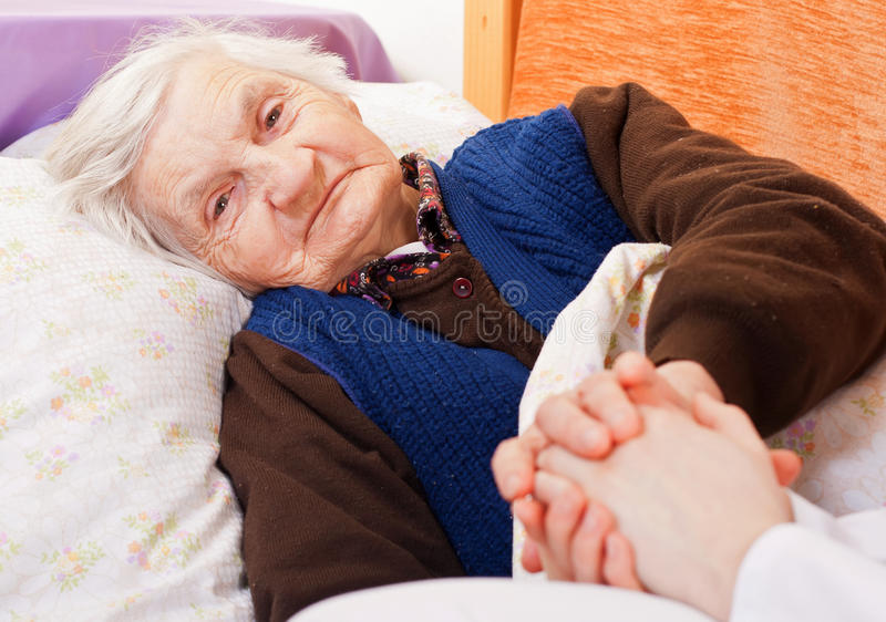 Elderly lonely woman rests in the bed royalty free stock photo