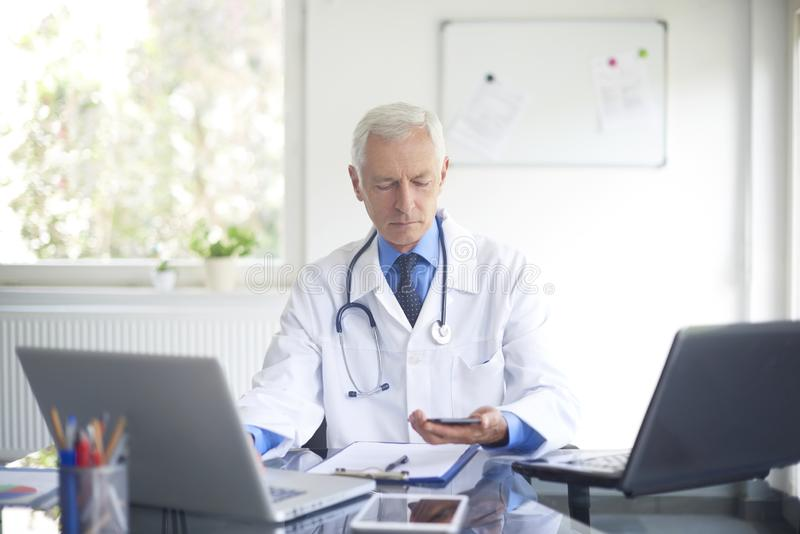Elderly male doctor working in private clinic. Elderly male doctor using his mobile phone and working on laptop while sitting at private clinic royalty free stock photography