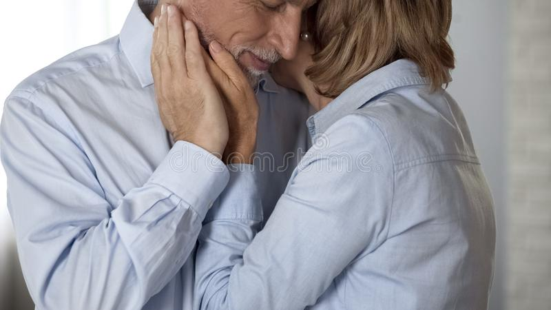 Elderly male and female hugging, lady cupping male cheek, happy long marriage stock photo