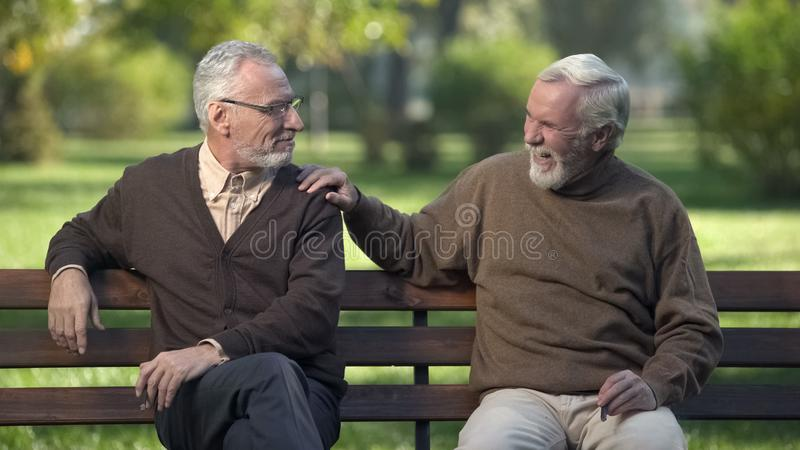 Elderly male friends smoking cigar, friends enjoying rest in park together stock photo