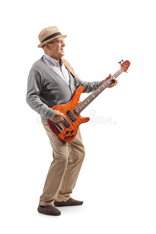 Elderly male guitarist playing a bass guitar royalty free stock photo