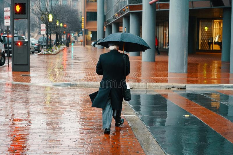 Elderly male person in a long coat walking with an umbrella during a rainy day royalty free stock photos