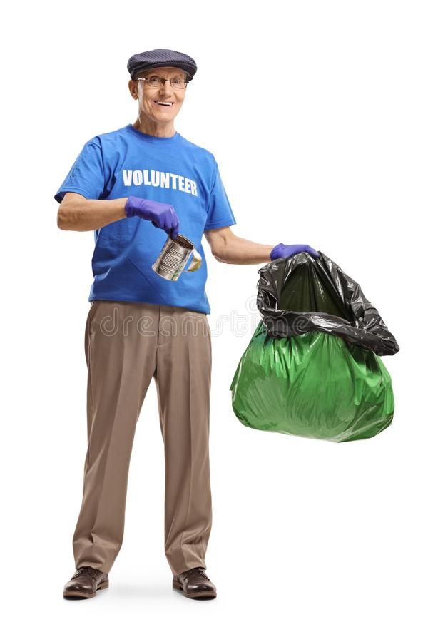 Elderly male volunteer putting a tin can in a plastic garbage bag stock photo