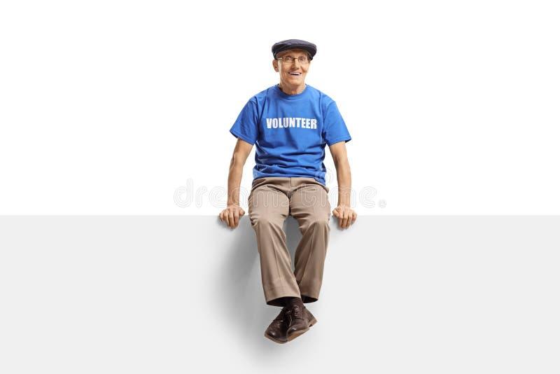 Elderly male volunteer sitting on blank white panel stock photos