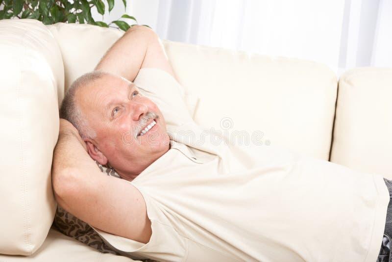 Elderly man. Happy smiling elderly man on the sofa stock photos