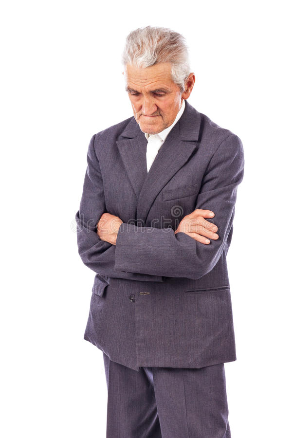 Elderly man with arms folded looking down lost in deep thought. On white background stock photos
