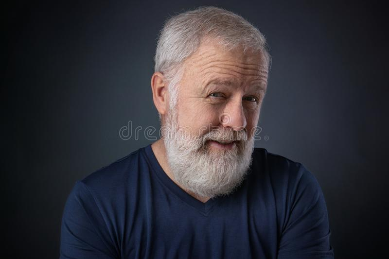 Elderly man with beard looking skeptical stock photography