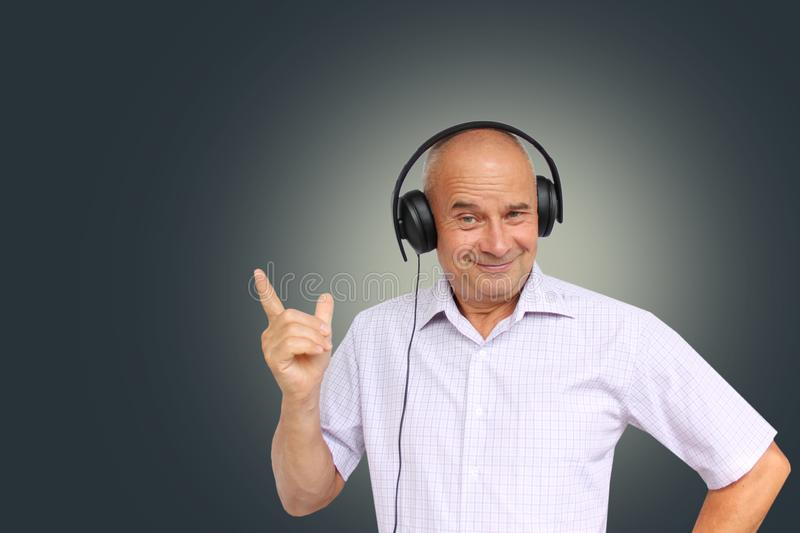 Elderly man in black headphones with emotions on his face gestures, isolate, photograph, concept, close-up, copy space royalty free stock photo