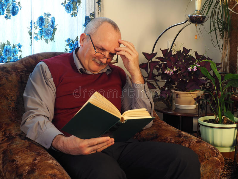 The elderly man with a book in a chair royalty free stock image
