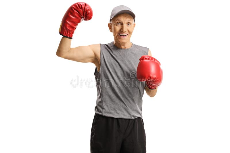 Elderly man with boxing gloves showing muscles stock photos