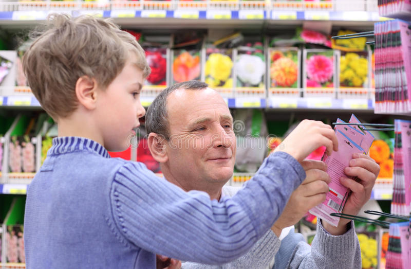 Elderly man with boy in shop of seeds royalty free stock photos