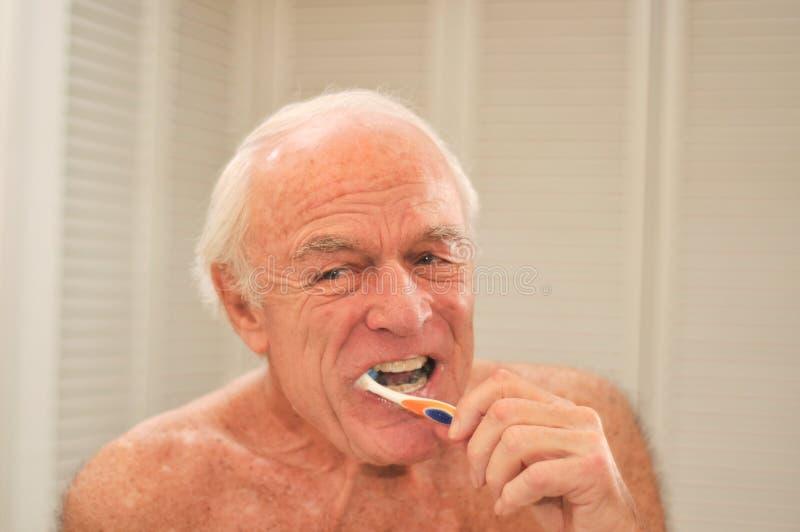 Elderly man brushing his teeth stock images