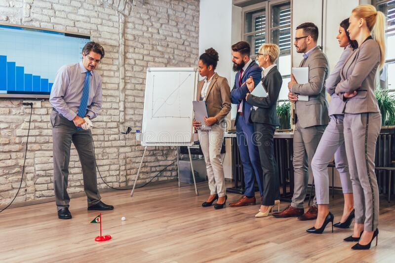 Elderly man in a business suit playing mini-golf in his office. Nearby are his assistants and watching. Respectable elderly men in a business suit playing mini royalty free stock image