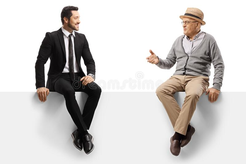 Elderly man and a businessman sitting on a panel and talking royalty free stock images
