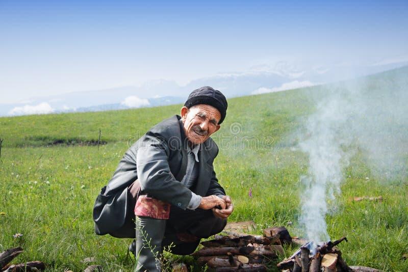 Elderly man at campfire royalty free stock photography