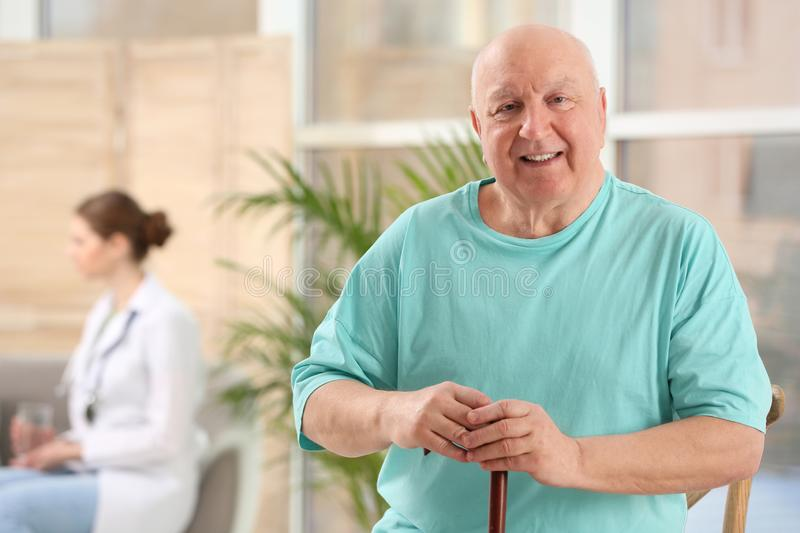 Elderly man with cane in nursing home. Assisting senior generation. Elderly man with cane in nursing home, space for text. Assisting senior generation stock image