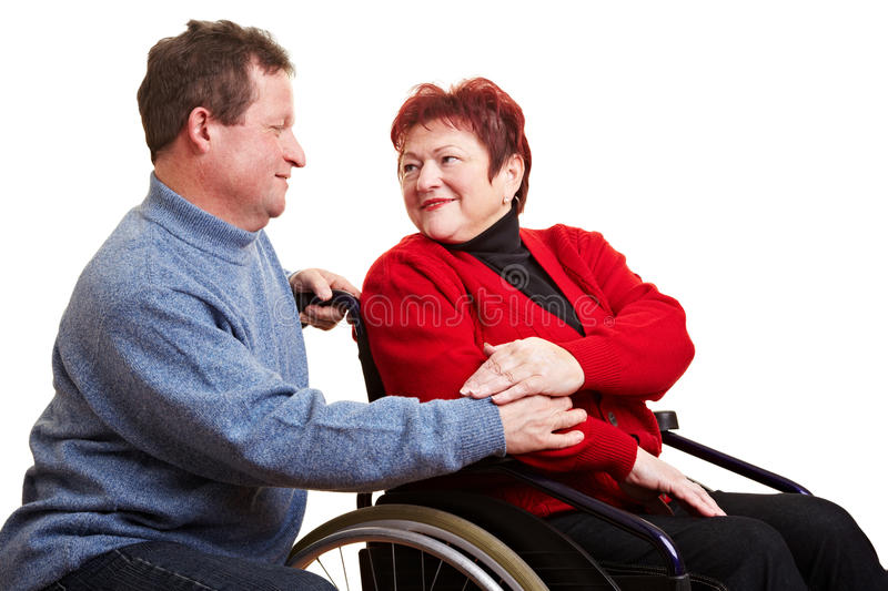 Elderly man caring for woman. Elderly man caring for his senior woman in wheelchair stock photos