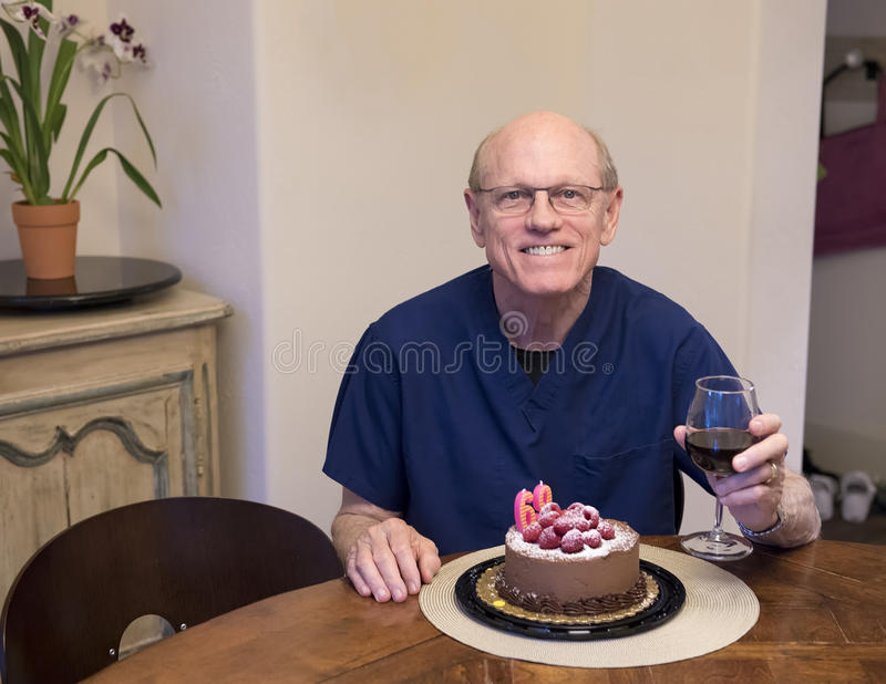 Elderly man celebrating his birthday. An elderly sixty-nine year old man is celebrating his birthday with a glass of red wine in his left hand. A chocolate-iced stock photo