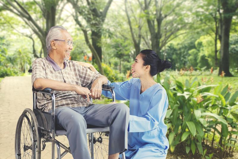 Elderly man chatting with his caregiver. Image of an elderly men sitting on the wheelchair and chatting with his caregiver in the park stock images