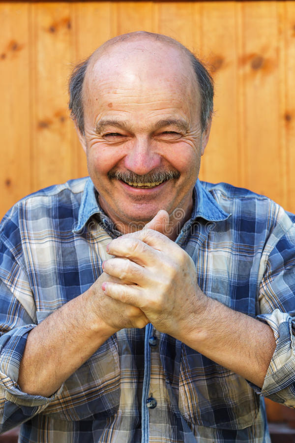 Elderly man claps his hands with delight stock images