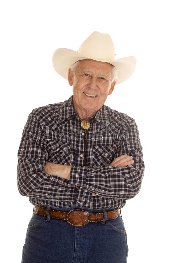 Elderly man cowboy arms folded. An elderly man in a cowboy hat standing with his arms folded stock photography