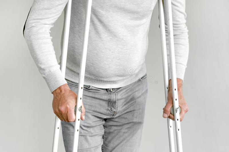 Elderly man with crutch. Close-up. Side view. Elderly man on crutches on a gray background. Close-up a elderly man walking with crutches royalty free stock image