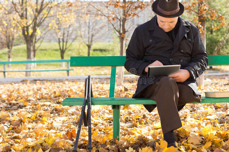 Elderly man on crutches using a tablet computer. As he sits outdoors in the sunshine in a warm overcoat on a chilly autumn day stock image