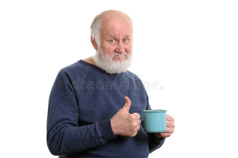 Elderly man with cup of bad tea or coffee showing thumb up isolated on white. Neutral elderly white haired man showing thumb up with blue cup of tea or coffe stock image