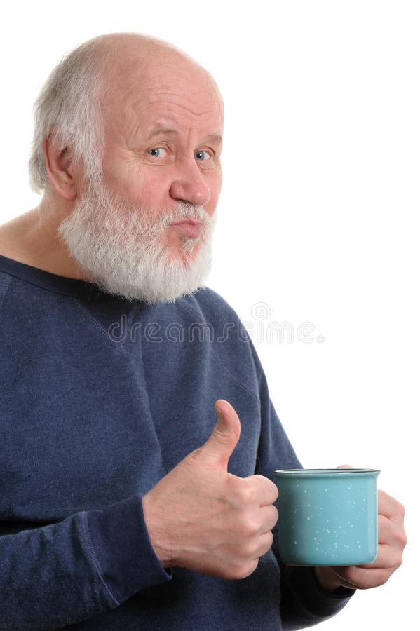 Elderly man with cup of bad tea or coffee showing thumb up isolated on white. Neutral elderly white haired man showing thumb up with blue cup of tea or coffe stock images