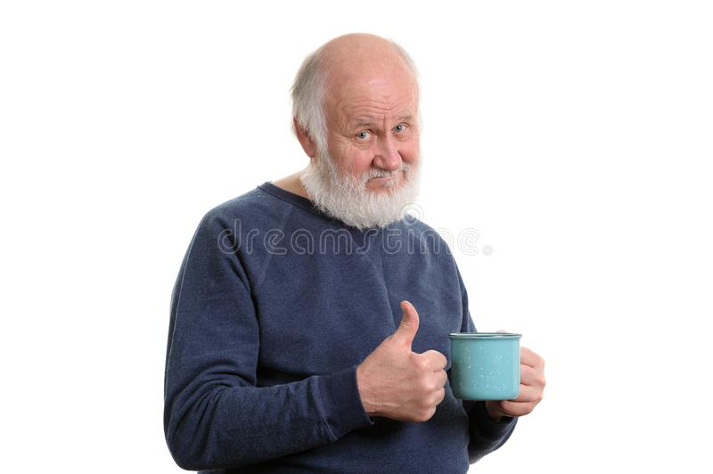 Elderly man with cup of bad tea or coffee showing thumb up isolated on white. Neutral elderly white haired man showing thumb up with blue cup of tea or coffe stock photography