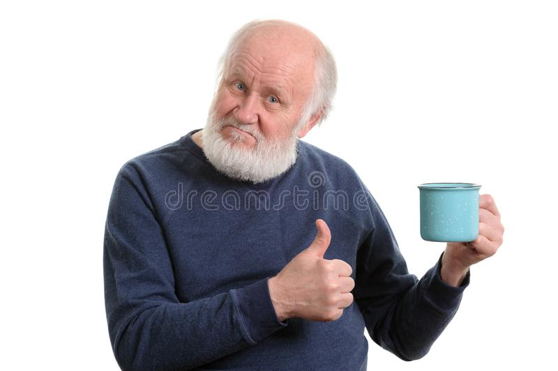 Elderly man with cup of bad tea or coffee showing thumb up isolated on white. Neutral elderly white haired man showing thumb up with blue cup of tea or coffe royalty free stock photos
