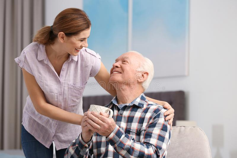 Elderly man with cup of tea near female caregiver at home. stock photo